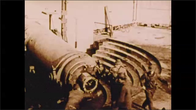 1900s: Factory makes weapons.  Row of weapons fire.  Men load and fire cannon.  Dignitaries walk.