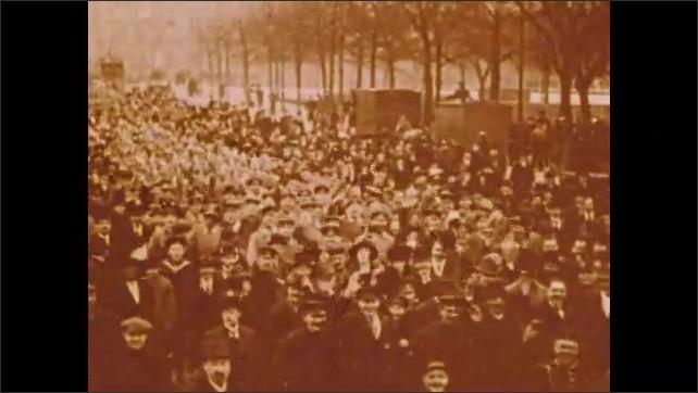 1900s: Men march down street.  Men raise hats.