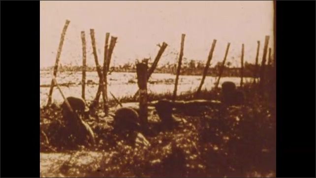 1900s: Soldiers march.  People carry belongings.  Barbed wire.  Men in foxholes.  Military parade.