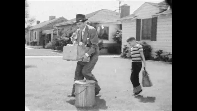 1950s: Garbage trucks leave waste management facility. Man carries garbage to curb with son. Boy hands briefcase to man and says goodbye. Man climbs into car.