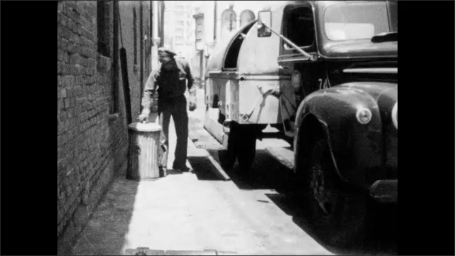 1950s: Trash collector exits truck and lowers steps. Man slides open door on back of garbage truck. Man empties trash can into back of truck and rides on step. Man sits trash can on ground.