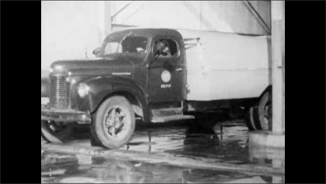 1950s: Dispatcher colors in area on map with pencil. Garbage truck backs into elevated hopper bay. Men exit truck and push wench controls.