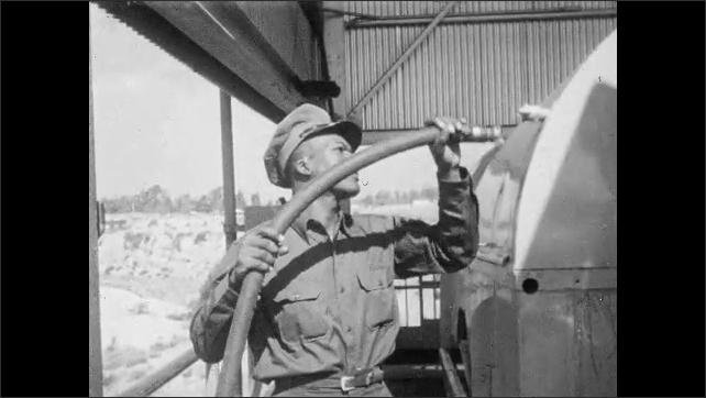 1950s: Man connects winch hook to garbage truck bin. Man attaches water hose to bin. Winch lifts bin of trash truck upwards. Man operates winch controls.