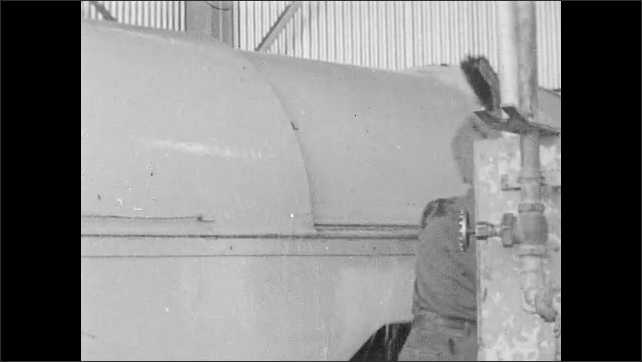 1950s: Man lowers bin on garbage truck. Men wash doors and cover of garbage truck with water and brushes. Man climbs into truck cab.