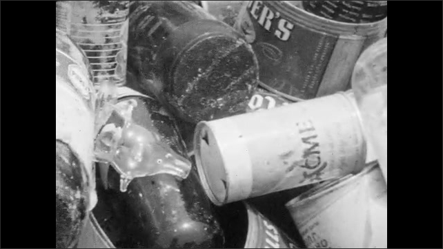 1950s: Worker dumps drum of rubbish into back of garbage truck. Boy hands man a tin can. Worker tosses can and steps onto truck. Can lands in pile of bottles and cans. Rubbish jiggles in truck.