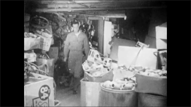 1950s: Broken glass and cullet pour from chute onto large pile. Man walks around storage room full of broken toy parts. Man retrieves doll leg from box.