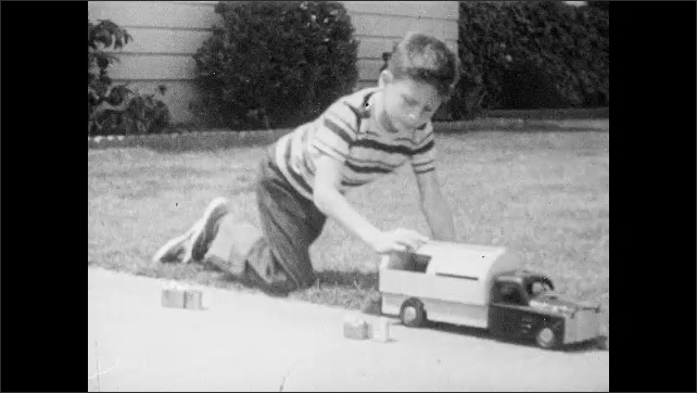 1950s: Boy empties pretend garbage into back of toy garbage truck. Piglet stands in pen. Boy empties pretend garbage into back of toy garbage truck. Glass bottles. Spool of copper wire.