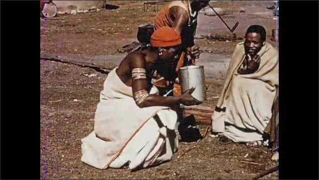 1950s SOUTH AFRICA: Women kneel and work. Men beat animal skin. Man drinks from pitcher. Man speaks.
