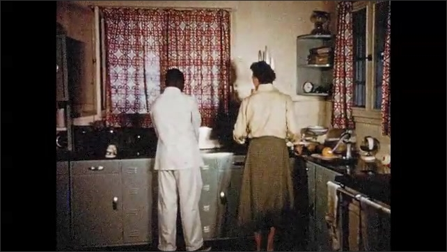 1950s SOUTH AFRICA: Family climbs into vehicle. Man places firewood by fireplace while women sews. Woman and employee work in kitchen. Man speaks to workers on farm.