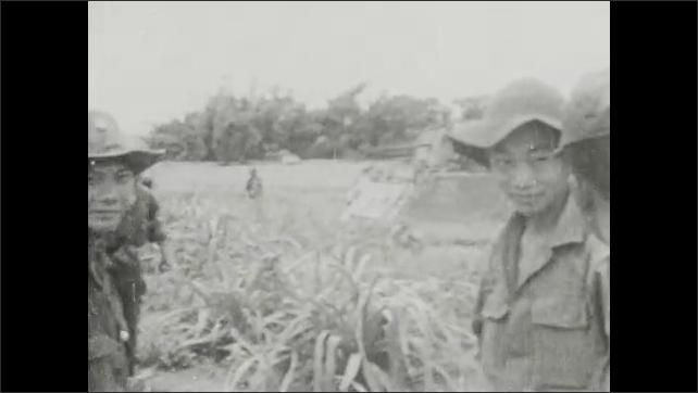 1960s: VIETNAM: prisoner on ground. Soldiers point gun at man's head. Soldiers whip prisoner. Soldiers punch prisoner