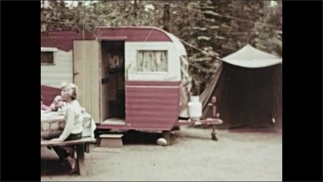 1960s: Family eats at picnic table near small house trailer at campsite. Pickup truck pulls mobile home down road.