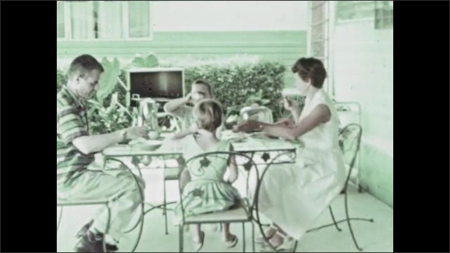 1960s: Family eats breakfast together at patio table. Boy pulls loose tooth from mouth at table. Boy hands tooth to woman. Baby tooth in woman's palm.