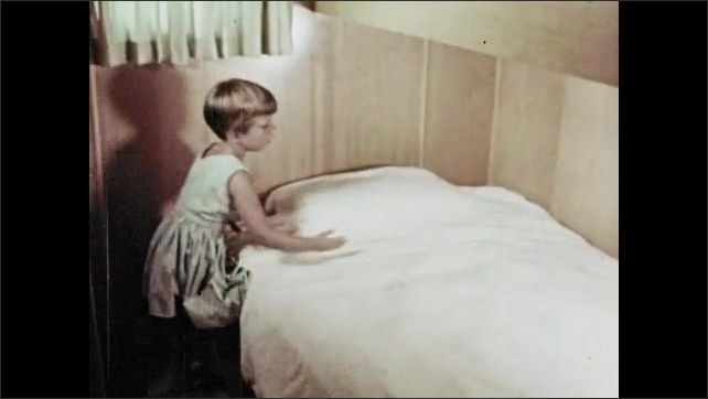 1960s: Girl makes bed. Girls smooths sheets on bed.