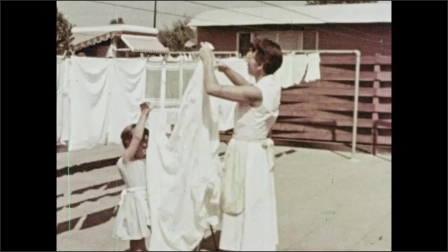 1960s: Woman and girl hang laundered sheets on clothes line. Girl and woman enter mobile home through sliding doors.