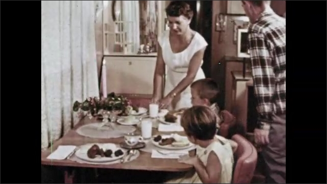 1960s: Family gather at dining table for dinner. Man pushes woman's chair in for her. Woman speaks to children.