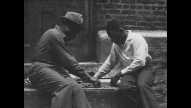 1950s HARLEM NEW YORK: Policemen watch protest and ride horses in street. Vacant lot. African-American men play checkers on stoop as policeman watches threateningly.