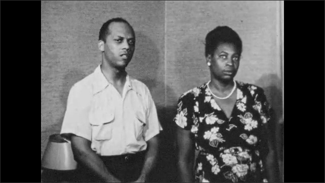 1950s HARLEM NEW YORK: African-American man and woman stand together solomonly. Man speaks of an attack in Harlem.