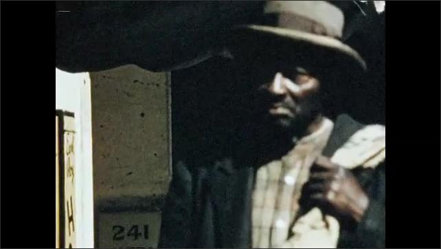 1960s: UNITED STATES: men smoke outside shop. Man walks in street.