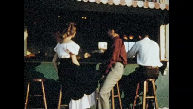 1960s: UNITED STATES: man talks to lady. Lady laughs with boy. Girl and boy go on date. Girl drinks in club. Tahiti cocktails sign