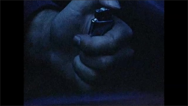 1960s: UNITED STATES: cigarette in hand. Man gives cigarette to girl in car at night. Lighter in hand. Girl with cigarette in hand. Hand lights cigarette