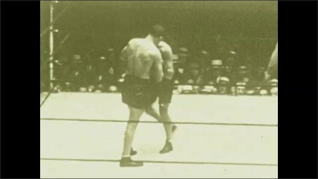 1920s: Men fight, grapple, punch in boxing ring, audience watches. Referee circles, separates men.