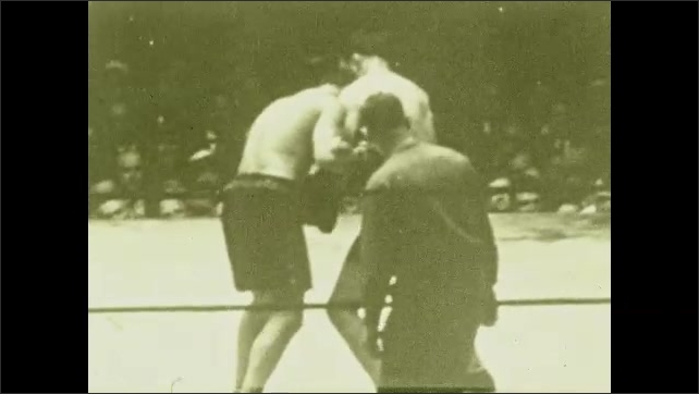 1920s: Men fight, grapple, punch in boxing ring, audience watches. Man punches other man repeatedly in stomach, referee intervenes.