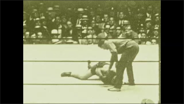 1920s: Men fight in boxing ring. Referee intervenes, man sucker punches other man, man falls, struggles to stand. Audience gets rowdy. Referee counts, waves arms. People rush to help man up.