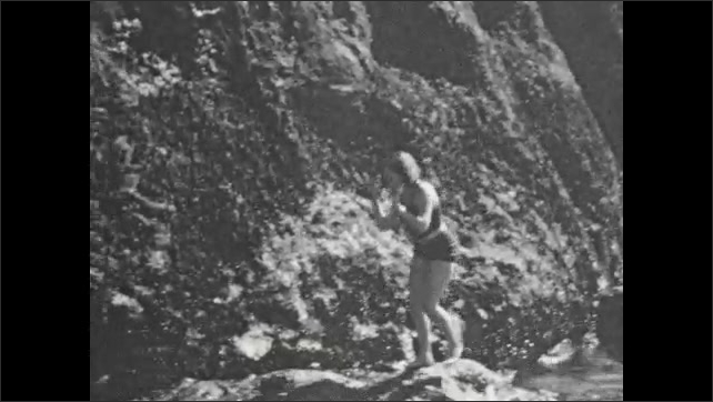 1920s: Steep, rocky shoreline, woman in swimsuit balances, looks nervous, scrambles across rocks, clings to cliffside, water flows in and out. Small campfire burns against rocks.