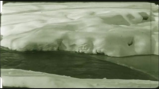 1940s: creek flowing while banks covered with snow, yard covered in snow