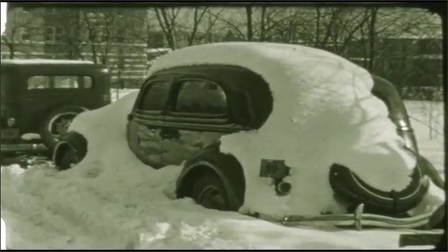 1940s: area surrounding apartment buildings covered in snow, parked cars covered in snow