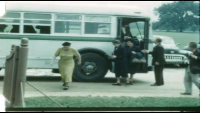 1940s: UNITED STATES: visitors to estate walk across footbridge. Ladies get off coach. Lady in dress smiles at camera. Visit to historical building.