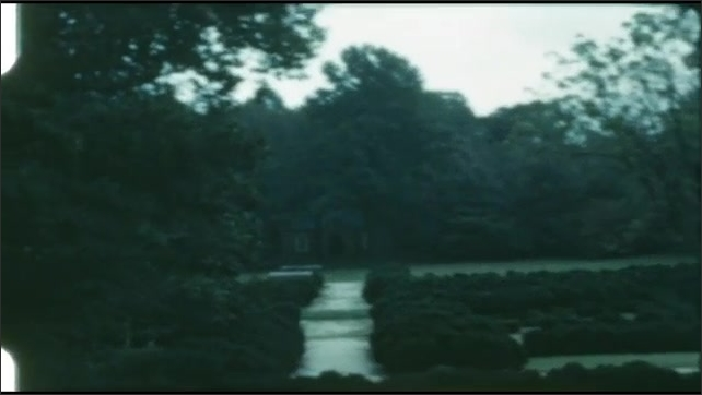 1940s: UNITED STATES: lady speaks to tour visitors. Tour guide introduces building to guests. View across gardens.