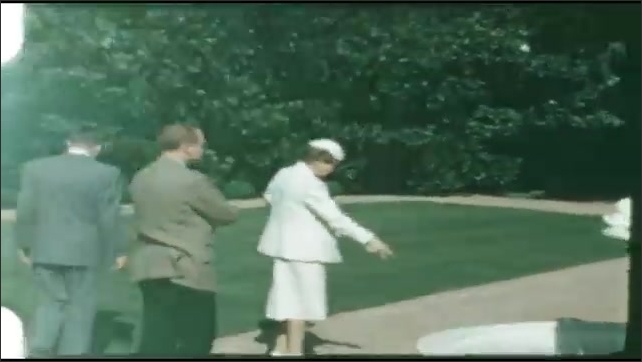 1940s: UNITED STATES: ladies stand and wait on balcony of building. Lady and men look at flowers in garden. Statue and garden fountain.