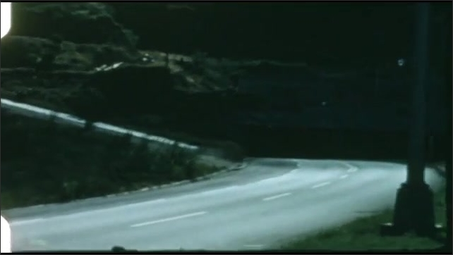 1940s: Buildings on hillside. Ocean and coastline. Car drives along road, through tunnel.