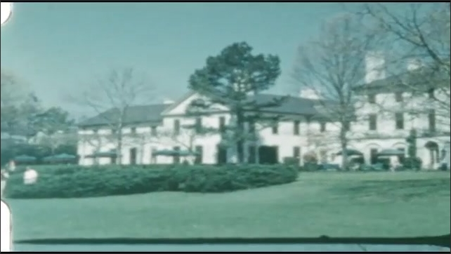 1940s: People in courtyard. Large building and grounds.