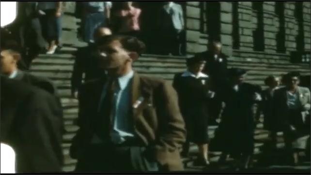 1940s: People walk down steps in front of building, walk down sidewalk.