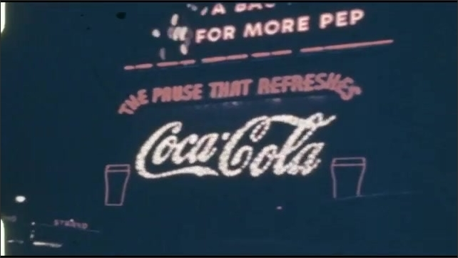 1940s: UNITED STATES: Coca Cola advert in lights at night. Planter's Peanuts advert.
