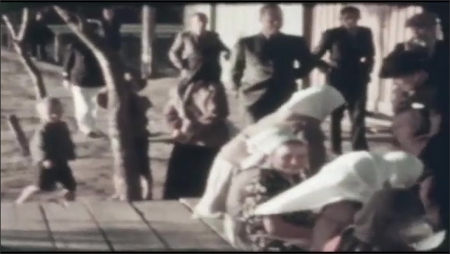 1940s: UNITED STATES: people walk in street at market. Ladies smile at cameras. Men row boats.