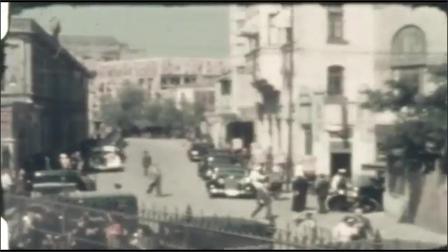 1940s: UNITED STATES: View across deck of ship towards coastline and settlement. People and cars in street. People carry goods on back.