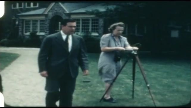 1940s: Woman and man set up camera tripod. Woman positions tripod. Group of people prepare to have photograph taken in front of building.