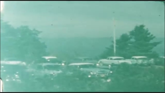 1940s: UNITED STATES: horses pull people on cart. Visitors on horse and buggy ride. Cars parked up. Rocks by view point.