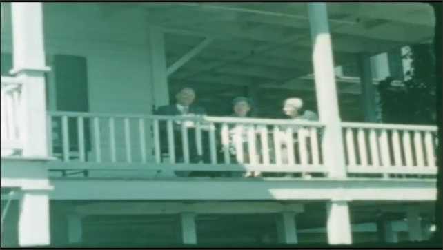 1940s: UNITED STATES: view of water from view point. People sat on balcony of house. Ashokan Reserve sign.