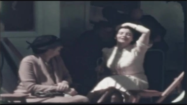 1940s: two women talking and laughing on deck, three men sitting in reclining lounge chairs, people smiling and talking on deck