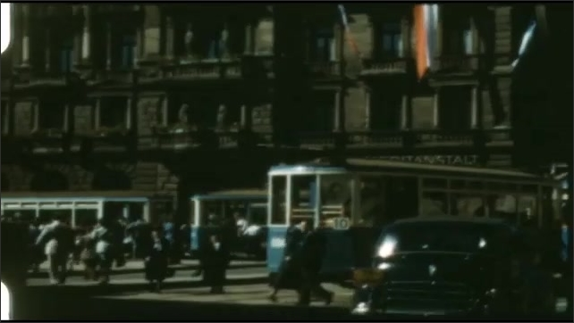 1940s: People board cable cars. Large ornate building. Clocktower.