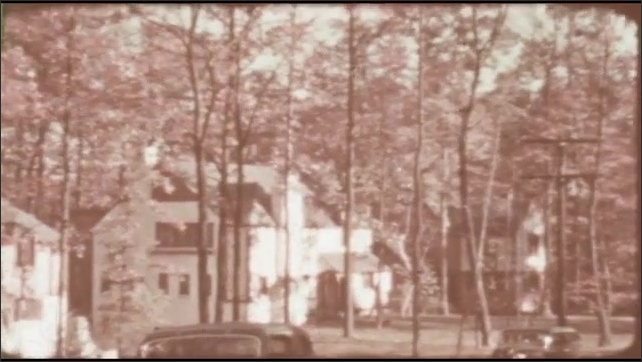 1940s: UNITED STATES: Rollingwood Homes of Distinction sign. Close up of sign and crest. Homes and gardens in woods. Lady walks to house. Car outside house.