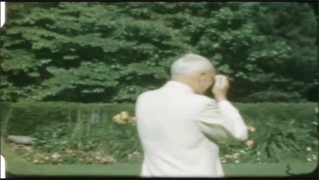 1940s: UNITED STATES: man films wedding reception. Guests in garden at wedding reception. Man takes photos of wedding party.
