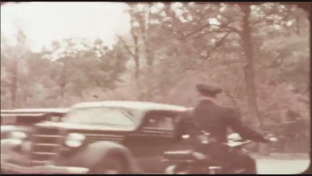 1940s: Police on motorcycles talk to people in car. Cars drive by. Leaves on tree in park.
