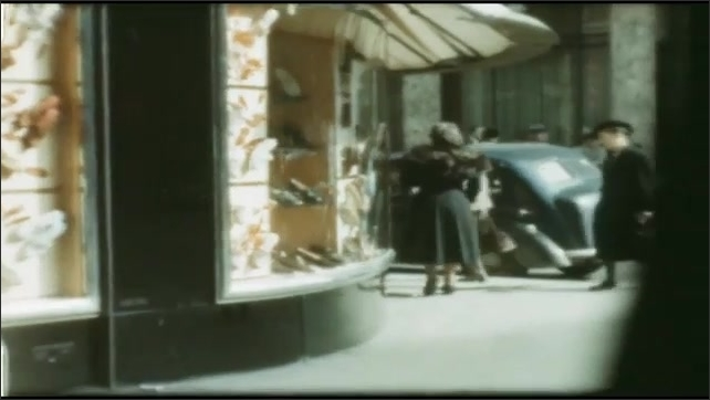 1940s: Pedestrians cross street in city. People walk passed store front. Pedestrians walk down sidewalk in city.