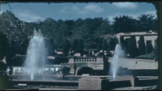 1940s: UNITED STATES: water features in large gardens and grounds. Clouds in blue sky. Lady walks past pond.