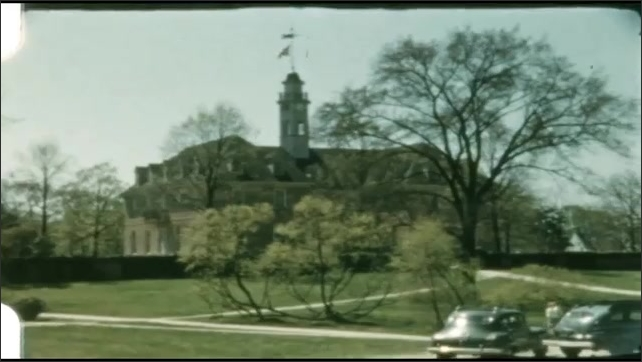 1940s: UNITED STATES: building and tower in gardens. Trees in grounds. Lady in garden. Girls play on lawn